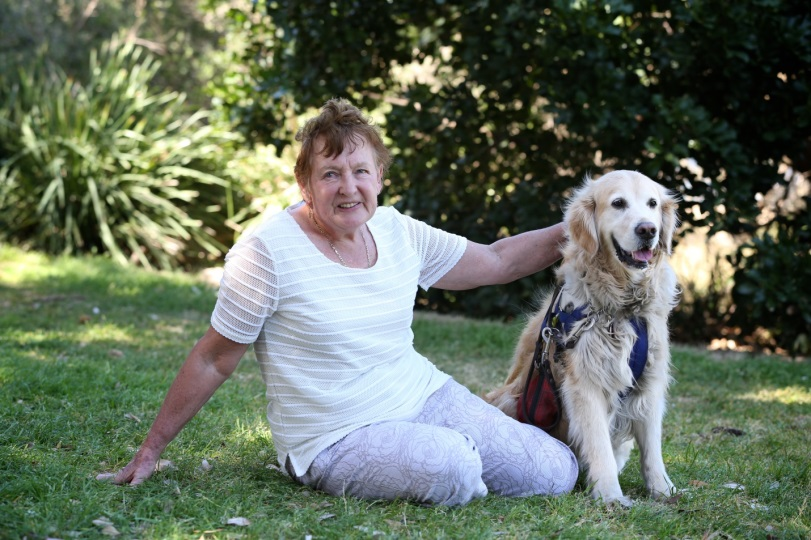 Woman and Golden Retriever sit outdoors on grass facing the camera